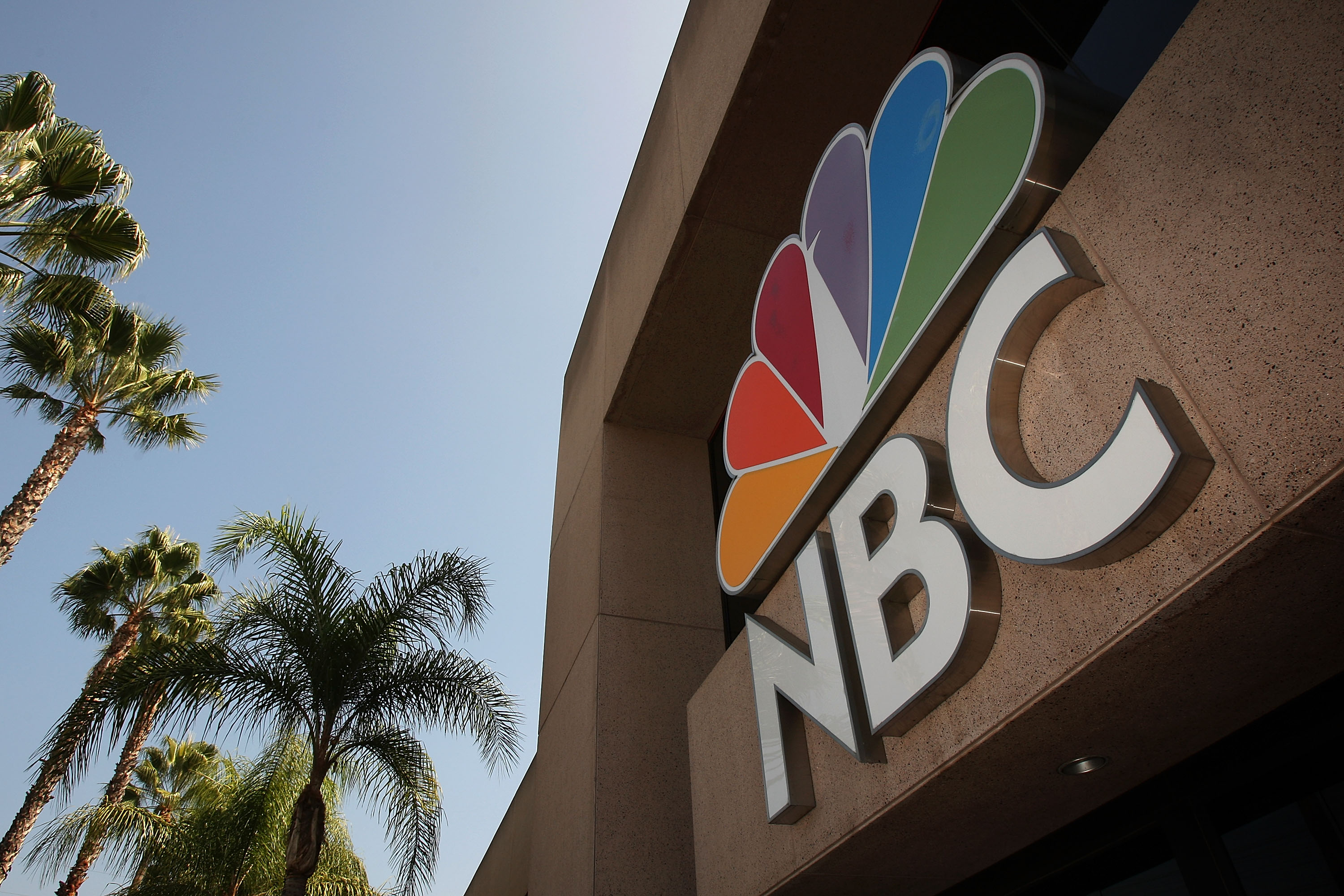 BURBANK, CA - OCTOBER 20: The NBC peacock logo hangs on the NBC studios building on October 20, 2008 in Burbank, California. NBC Universal plans another round of major cuts totaling $500 million from the next yearly budget in spite of recent strong quarterly reports. The cuts come as the media sector copes with recent market turmoil that sent stock prices for many major conglomerates plunging to all-time lows, as much as 70 percent for the past year. NBC Universal stations are facing a serious local ad slump while its parent company, General Electric, is facing financial problems with heavy reliance on financial services in an environment of frozen credit. (Photo by David McNew/Getty Images)